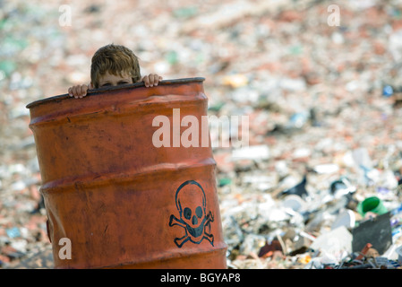 Child peeking over edge of metal barrel marked with skull and bones, surrounded by landfill - Stock Photo