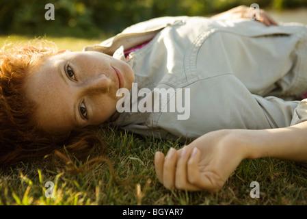 Young woman lying on back in grass - Stock Photo