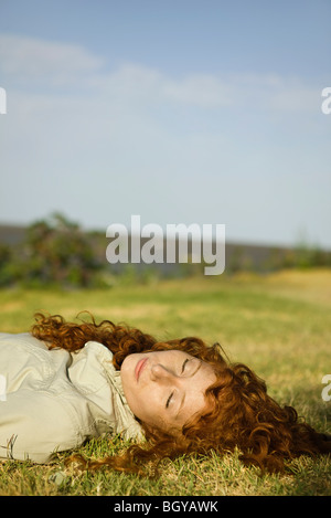 Young woman with eyes closed lying on back in grassy field - Stock Photo
