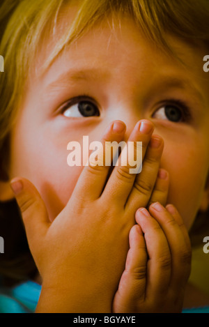Child covering mouth with hands looking up expectantly - Stock Photo