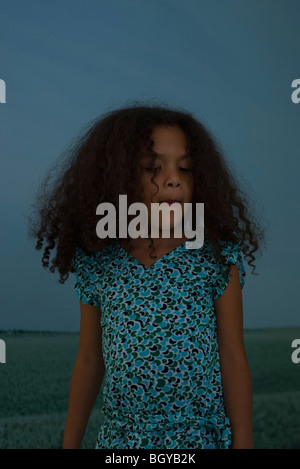 Little girl with curly hair biting lip, portrait - Stock Photo
