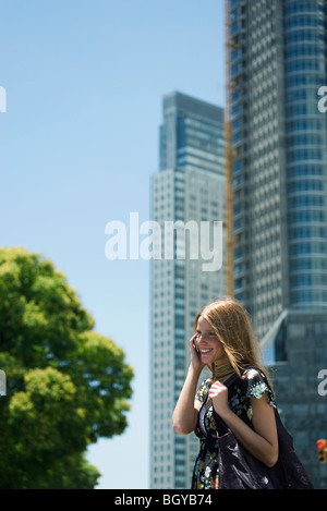 Young woman talking on cell phone, high rise buildings in background - Stock Photo