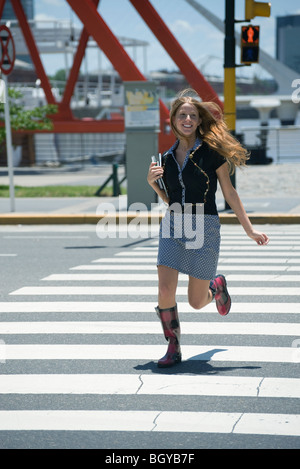 Young woman running across crosswalk while walk signal is red - Stock Photo