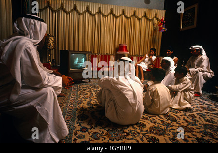 July 20, 1969.  Apollo landing of a man on the moon viewed on television by a family in Kuwait.  Arab men and women - Stock Photo