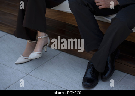 Man and woman sitting on bench indoors, low section - Stock Photo