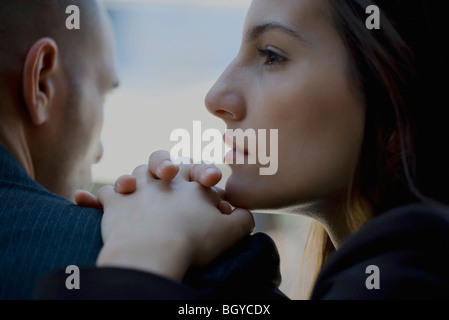 Woman resting chin on clasped hands placed on man's shoulder - Stock Photo