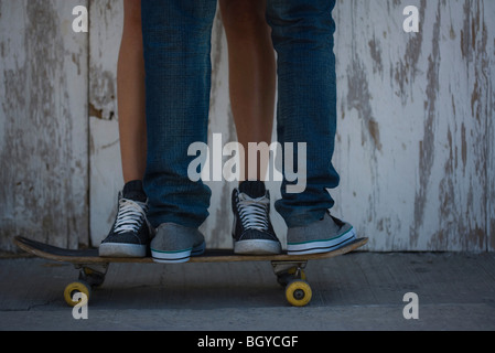 Legs of couple together on skateboard - Stock Photo