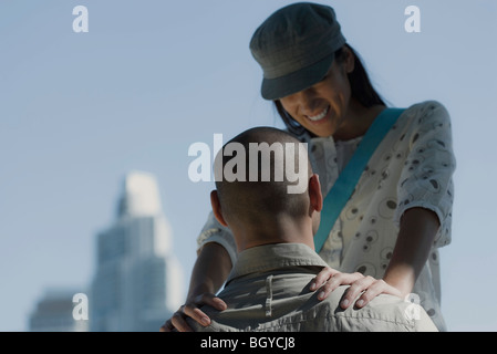 Young couple, man seated, woman standing in front with hands placed on man's shoulders looking down smiling - Stock Photo