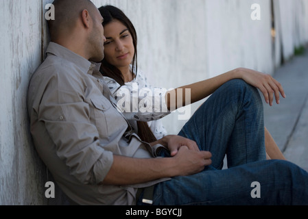 Young couple sitting side by side on ground, leaning against wall having conversation - Stock Photo