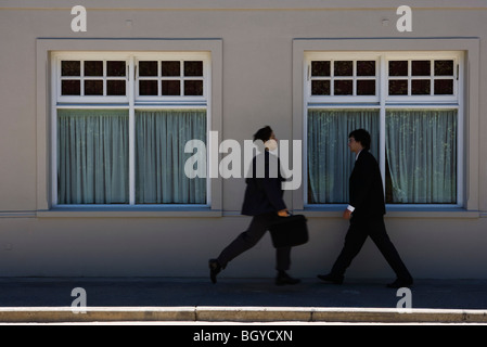 Two young businessmen hurrying toward each other on sidewalk - Stock Photo