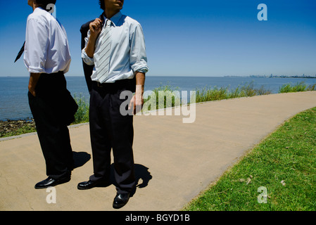 Two young businessmen standing on path, sea in background, cropped - Stock Photo