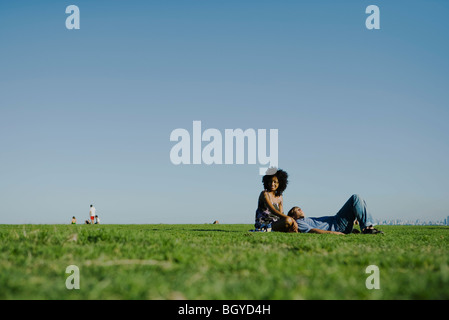 Young couple relaxing together in park - Stock Photo