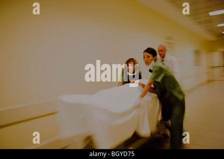 Healthcare workers rushing patient on gurney in hospital corridor - Stock Photo