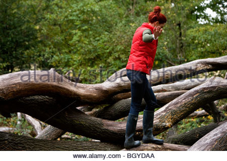 A young woman balancing on a fallen tree - Stock Photo