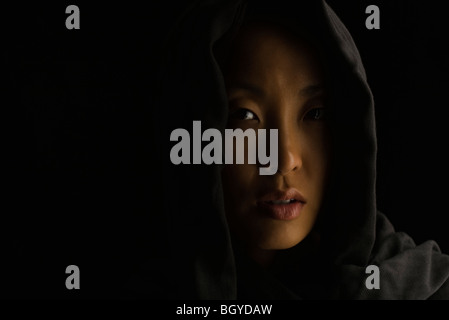 Woman wearing hood, looking apprehensively at camera - Stock Photo