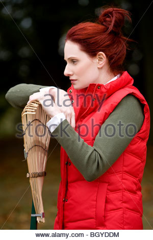 A young woman leaning on a rake - Stock Photo