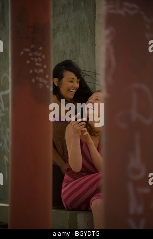 Two young women friends looking at cell phone together, laughing - Stock Photo