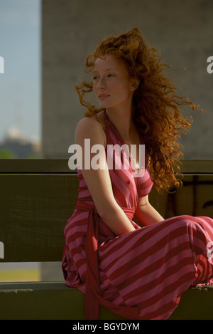 Young woman sitting outdoors, wearing dress, hair blowing in wind - Stock Photo