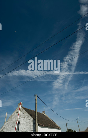 Vapor trails and airplane in blue sky above rustic house - Stock Photo
