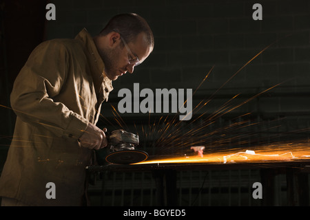 Steel grinder working in metal shop - Stock Photo