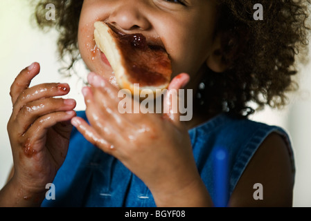Little girl eating snack, hands and face covered in jam - Stock Photo