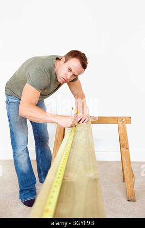 Man measuring wooden plank - Stock Photo
