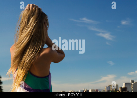 Female standing with hands in hair, looking at city in distance - Stock Photo