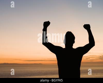 Silhouette of man raising arms - Stock Photo