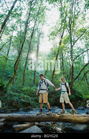 Hikers walking on log - Stock Photo