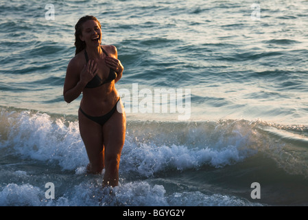 Woman running through surf at beach, laughing - Stock Photo