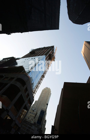 Manhattan skyscraper under construction surrounded by other high rise buildings, low angle view, NYC - Stock Photo