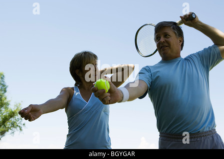 Tennis player coached on serve form - Stock Photo