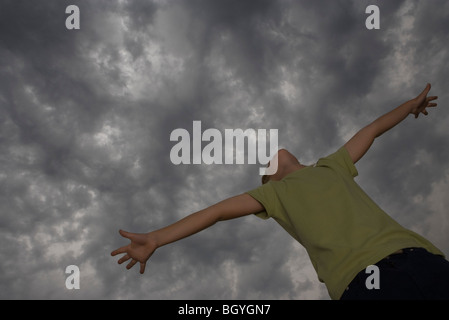 Boy with arms outstretched, head back, looking up at gray sky - Stock Photo