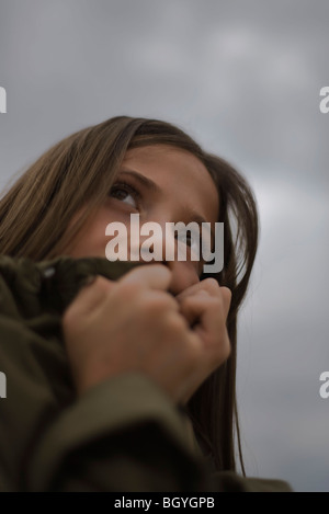 Female covering mouth with hands looking away fearfully - Stock Photo