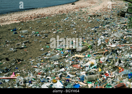 Beach strewn with washed up garbage - Stock Photo