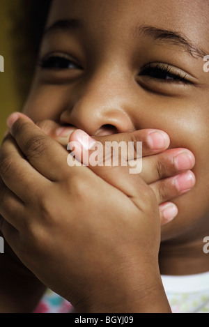 Little girl covering mouth with hands - Stock Photo