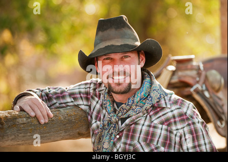 Cowboy leaning on fence - Stock Photo