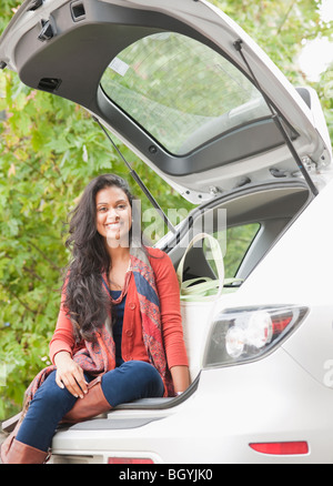 Woman sitting in trunk of car - Stock Photo