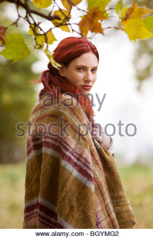 A young woman standing outdoors, wrapped in a blanket - Stock Photo