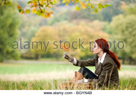 A young woman sitting in the grass, looking at a leaf - Stock Photo