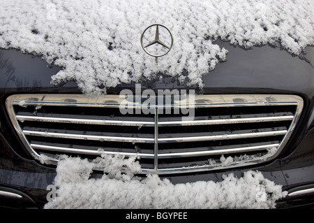 A snow covered Mercedes car showing the grille and badge - Stock Photo