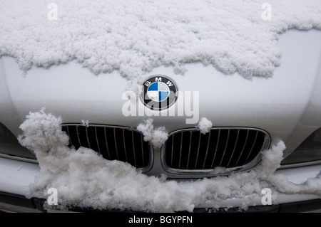 A snow covered BMW car showing the grille and badge - Stock Photo
