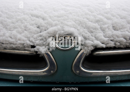 A snow covered NISSAN car showing the grille and badge - Stock Photo
