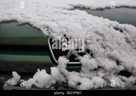 A snow covered Peugeot car showing the grille and badge. - Stock Photo