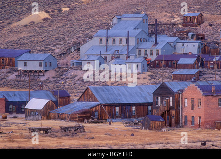 Bodie ghost town at dusk with old Standard Stamp Mill buildings on hillside; Bodie State Historical Park, California. - Stock Photo