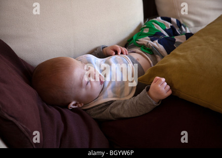 Six month old baby boy sleeping on the sofa. London,England - Stock Photo