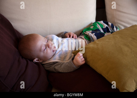 Six month old baby boy sleeping on the sofa. London,England. - Stock Photo
