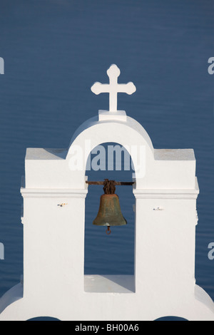 St. Gerasimos Christian Church bell tower and cross in Firostefani, against blue background of the Mediterranean - Stock Photo