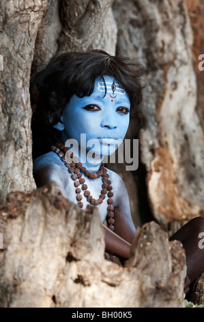 Indian boy, face painted as the Hindu god Shiva sitting in an old tree stump. Andhra Pradesh, India - Stock Photo