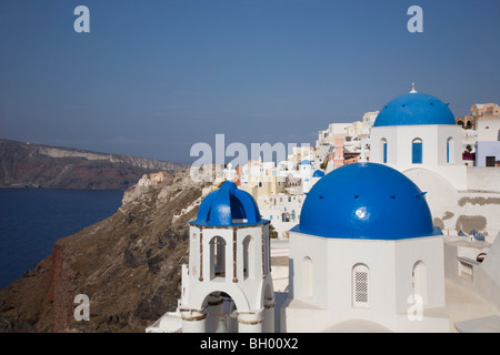 Clifftop town of Oia with blue-domed white churches overlooking Santorini's caldera and lagoon in the Mediterranean - Stock Photo